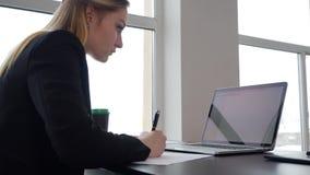 Empresaria joven que hace notas en el lugar de trabajo almacen de video