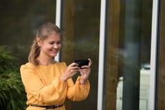 Empresaria joven que juega con el teléfono celular imagenes de archivo