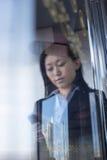 Empresaria joven que mira abajo de y que usa el teléfono en el otro lado la ventana de cristal Fotografía de archivo