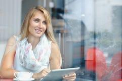 Empresaria joven que mira la pantalla de la almohadilla táctil mientras que se coloca en café fotografía de archivo