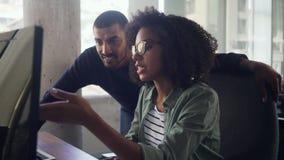 Empresaria joven que muestra algo en el ordenador a su colega almacen de metraje de vídeo