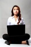 Empresaria joven que piensa mientras que trabaja con un ordenador portátil Imagenes de archivo