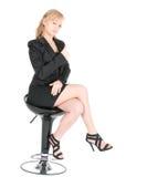 Empresaria joven que presenta en una silla de la barra sobre el fondo blanco Imagen de archivo