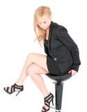Empresaria joven que presenta en una silla de la barra sobre el fondo blanco Foto de archivo libre de regalías