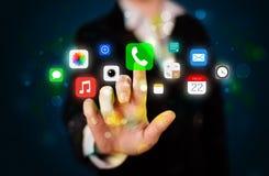 Empresaria joven que presiona iconos coloridos del app del móvil con el boke
