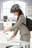 Empresaria joven que sale de la oficina en bici Imágenes de archivo libres de regalías