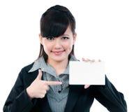 Empresaria joven que señala en la tarjeta en blanco Fotos de archivo libres de regalías