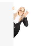 Empresaria joven que se coloca detrás de un panel en blanco Fotografía de archivo