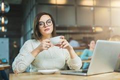 Empresaria joven que se sienta en café en la tabla, el café de consumición y trabajando en el ordenador portátil El estudiante es Fotos de archivo libres de regalías