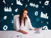 Empresaria joven que se sienta en el escritorio con los diagramas y las estadísticas Imagen de archivo libre de regalías