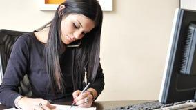 Empresaria joven que se sienta en el escritorio en la oficina ocupada en el teléfono almacen de video