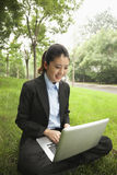 Empresaria joven que se sienta en el parque y que trabaja en su ordenador portátil Imagenes de archivo