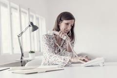 Empresaria joven que se sienta en su escritorio de oficina que hace un telephon foto de archivo libre de regalías