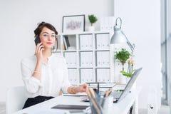 Empresaria joven que se sienta en su lugar de trabajo, resolviendo las nuevas ideas del negocio, traje formal que lleva y vidrios fotos de archivo