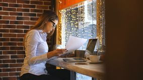 empresaria joven que se sienta en un café y que estudia documentos almacen de metraje de vídeo