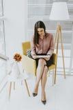 Empresaria joven que se sienta en una silla y que sostiene la tableta en Han Fotografía de archivo