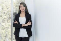 Empresaria joven que sonríe y que piensa en trabajo de proyecto en o fotos de archivo