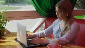 Empresaria joven que trabaja con el ordenador portátil en café almacen de video