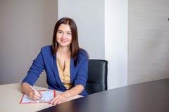 Empresaria joven que trabaja en el escritorio en oficina, tomando notas en el calendario personal, sonriendo fotografía de archivo
