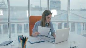 Empresaria joven que trabaja en el ordenador en la oficina almacen de video