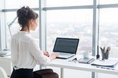 Empresaria joven que trabaja en la oficina, mecanografiando, usando el ordenador Mujer concentrada que busca la información en lí Foto de archivo