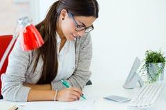 Empresaria joven que trabaja en su oficina con el ordenador portátil Imagenes de archivo