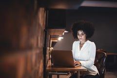Empresaria joven que trabaja tarde en el ordenador portátil en oficina imagen de archivo libre de regalías