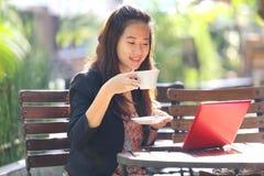 Empresaria joven que usa el ordenador portátil y bebiendo el café al aire libre Imágenes de archivo libres de regalías