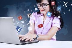 Empresaria joven que usa la red social con el ordenador portátil Imagen de archivo libre de regalías