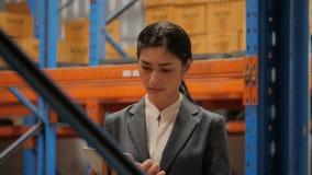 Empresaria joven que usa la tableta digital que comprueba la acción en almacén industrial