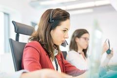 Empresaria joven que usa las auriculares con el colega femenino en fondo en la oficina Imagen de archivo libre de regalías