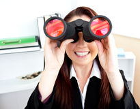 Empresaria joven que usa los prismáticos en su oficina Fotos de archivo