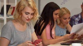 Empresaria joven que usa su teléfono elegante durante la reunión