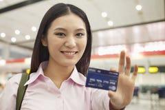 Empresaria joven sonriente dentro que se sostiene hacia fuera y mostrar la tarjeta de crédito Fotos de archivo libres de regalías