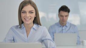 Empresaria joven sonriente Looking en la cámara en oficina almacen de metraje de vídeo