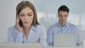 Empresaria joven Talking en el teléfono, discutiendo el trabajo almacen de metraje de vídeo