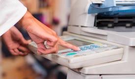 Empresaria joven Using Copy Machine en la oficina Foto de archivo libre de regalías