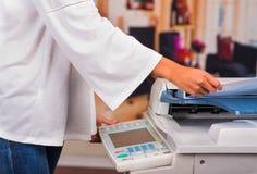 Empresaria joven Using Copy Machine en la oficina Imagen de archivo