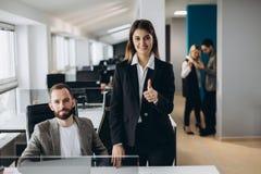 Empresaria joven y hombre de negocios que trabajan junto en oficina Pulgar hermoso de la demostración de la muchacha de oficina p imagen de archivo