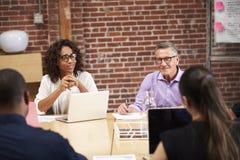 Empresaria Leading Office Meeting de los colegas que se sientan alrededor de la tabla imagenes de archivo