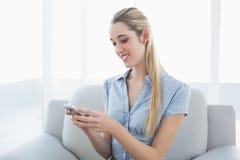 Empresaria linda que manda un SMS con su smartphone que se sienta en el sofá Foto de archivo