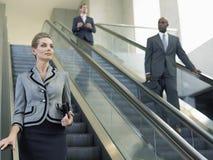 Empresaria Looking Away While que se mueve abajo en la escalera móvil Imagen de archivo libre de regalías
