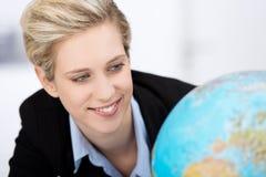 Empresaria Looking At Globe en oficina Imagen de archivo libre de regalías
