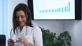 Empresaria madura confiada que se coloca en oficina Encargado de sexo femenino en la oficina que mira la cámara y la sonrisa Cáma almacen de video