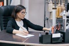 Empresaria madura en el lugar de trabajo, mujer en la oficina usando el ordenador, telas de la sala de exposición del fondo y acc imagenes de archivo