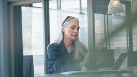 Empresaria madura que manda un SMS en su teléfono en la oficina almacen de video