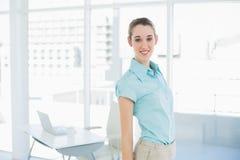 Empresaria magnífica que lleva la blusa azul que presenta en su oficina Foto de archivo libre de regalías