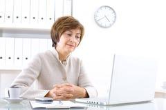 Empresaria mayor con la computadora portátil Fotos de archivo