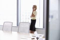 Empresaria mayor On Mobile Phone en la sala de reunión Fotografía de archivo