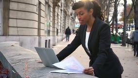 Empresaria a medias africana que hace la llamada video con el ordenador portátil afuera almacen de metraje de vídeo